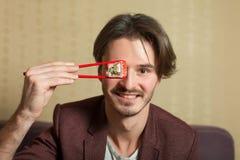Man show chopsticks with sushi roll. Stock Photos