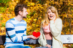 Man show feelings to girl in autumnal park. Royalty Free Stock Image