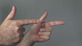Man show guns with his fingers stock video footage