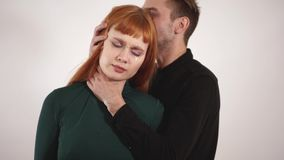 Man show his violence with strangling womans neck and then he laid girls head on his shoulder, hug female and stroke her. Young aggressive man show his violence stock video footage