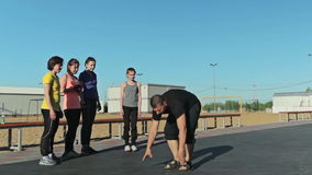 A man show how to do burpee, pushups and another exercise stock footage