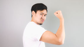 A man show off his arm. An asian man with white t-shirt and grey background stock photos