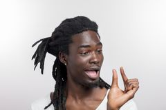 Dark skinned man showing small thing while smiling and standing near white background royalty free stock photo