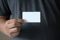 Man show white business card. Closeup shot  Man show white business card Plastic bank-card design mock up Stock Image