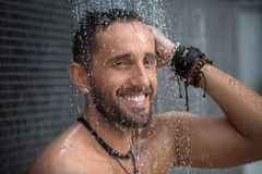 Man in shower. Calm tanned dark-haired man with a naked torso in the shower. Tropical. Horizontal photo Stock Photo