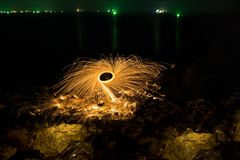 Man showers of glowing sparks from spinning steel wool on rocky royalty free stock photo