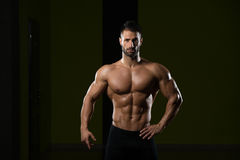 Man Showing Abdominal Muscle. Handsome Man Standing Strong In The Gym And Flexing Muscles - Muscular Athletic Bodybuilder Fitness Model Posing After Exercises stock image