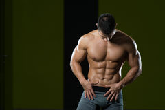 Man Showing Abdominal Muscle. Handsome Man Standing Strong In The Gym And Flexing Muscles - Muscular Athletic Bodybuilder Fitness Model Posing After Exercises royalty free stock photography