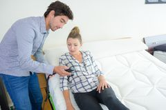 Man showing bed controls to woman stock photo