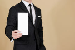 Man showing blank black flyer brochure booklet. Leaflet presentation. Pamphlet hold hands. Man show clear offset paper. Sheet. Template. Man in a black suit royalty free stock photo
