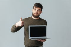 Man showing blank laptop computer screen and thumb up. Casual man showing blank laptop computer screen and thumb up over gray background Royalty Free Stock Images