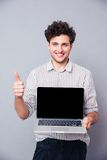 Man showing blank laptop screen. Happy casual man showing blank laptop screen and thumb up over gray background royalty free stock photos