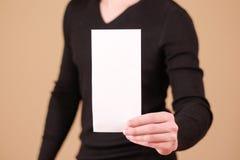 Man showing blank white flyer brochure booklet. Leaflet presentation. Pamphlet hold hands. Man show clear offset paper. Sheet. Template. Booklet design sheet stock image