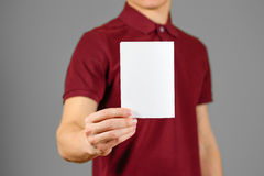 Man showing blank white flyer brochure booklet. Leaflet presentation. Pamphlet hold hands. Man show clear offset paper. Sheet template. Booklet design sheet Stock Image