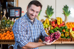 Man showing a bunch of grapes. Portrait of happy man in shirt showing a bunch of grapes in supermarket. Boxes with fruits and vegetables on the background Stock Image