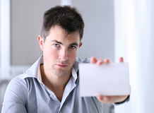 Man showing a business card. Man in office showing a business card Royalty Free Stock Image