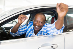 Man showing car key. Excited african man showing a car key inside his new vehicle Royalty Free Stock Photo