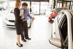 A man showing a car to the saleswoman Royalty Free Stock Photography