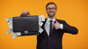 Man showing case packed with money, winking and doing thumbs-up, loan, credit