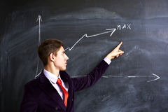 Man showing on the chalkboard. Young student showing at a graph on the chalkboard Stock Image