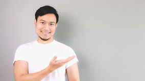 A man showing the content, copyspace. An asian man with white t-shirt and grey background royalty free stock images