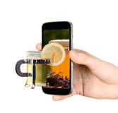 Man is showing cup with tea through mobile phone Stock Photos