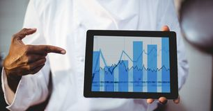 Man showing digital tablet displaying graph chart on screen Stock Photos