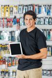 Man Showing Digital Tablet In Hardware Store. Portrait of confident young man showing digital tablet in hardware store Stock Photography