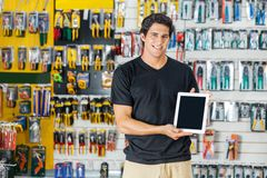 Man Showing Digital Tablet In Hardware Store. Portrait of confident young man showing digital tablet in hardware store Stock Photo