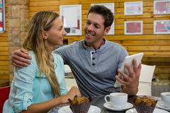 Man showing digital tablet to girlfriend in cafe stock image