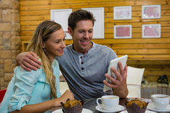 Man showing digital tablet to girlfriend in coffee shop royalty free stock photography