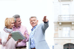 Man showing direction to couple with road map in city Stock Photos