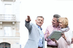 Man showing direction to couple with road map in city Royalty Free Stock Image