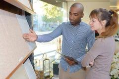 Man showing display tiles to customer. Man showing display of tiles to customer Stock Images