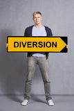 Man showing diversion sign. Friendly man holding diversion sign isolated on grey background Stock Photos