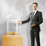 Man showing donation box. Young businessman in suit showing donation box on concrete background. 3D Rendering Stock Images