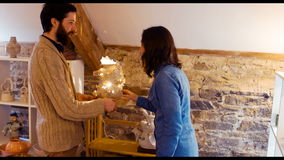 Man showing earthenware lamp to a woman stock video