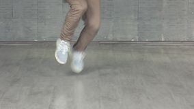 Man showing elements of contemporary dance. Feet of hip-hop dancer on grey background stock video footage