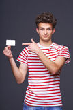Man showing empty blank paper card sign. Man showing pointing at empty blank paper card sign with copy space for text, grinning with skepticism, on gray royalty free stock images