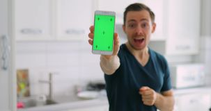 Man showing empty green screen of smart phone at home with delight. Man showing an empty green screen of smart phone at home with delight stock video