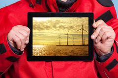 Man showing farm of wind turbines on tablet. Power Stock Photo
