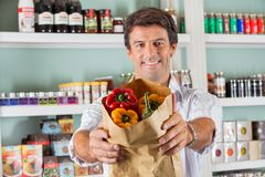 Man Showing Fresh Bellpeppers In Paper Bag Stock Images