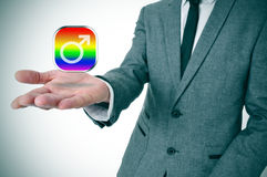 Man showing a gay male app icon. A man wearing a suit with an icon of an app for gay male in his hand Stock Image