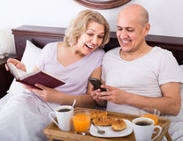 Man showing girlfriend something on book during breakfast Stock Photo
