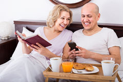 Man showing girlfriend something on book during breakfast Royalty Free Stock Photos
