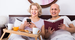 Man showing girlfriend something on book during breakfast Stock Photos