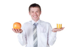 Man showing glass of orange juice and fruit to the Royalty Free Stock Photography