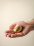 Man showing golden eggs, symbol of money saving. Man showing golden egg and holding it in hand. Concept of people securing savings, money, precious and valuable Royalty Free Stock Photography