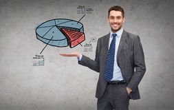 Man showing growing chart on the palm of his hand. Business, office, advertising and people concept - friendly young buisnessman showing growing chart on the Royalty Free Stock Photos