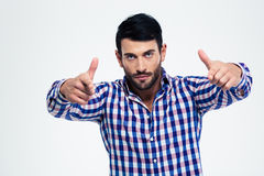 Man showing gun gesture with fingers at camera. Portrait of a serious handsome man showing gun gesture with fingers at camera isolated on a white background Royalty Free Stock Photos